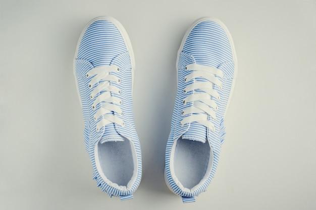 Blauwe gestreepte vrouwelijke tennisschoenen op een witte hoogste mening. plat lag minimaal