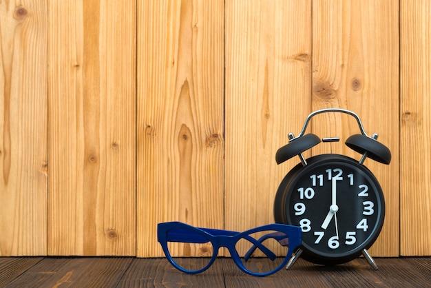 Blauwe glazen en zwarte uitstekende wekker op het hout.