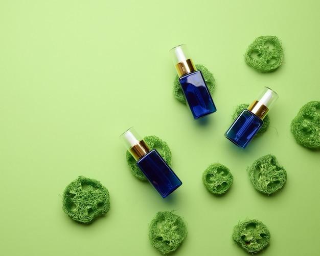 Blauwe glazen fles met een druppelaar voor cosmetica op een groene achtergrond. verpakkingen voor gel, serum, reclame en promotie. natuurlijke biologische producten. bespotten