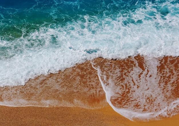 Blauwe golf op het strand. vervaag achtergrond en zonlichtvlekken.