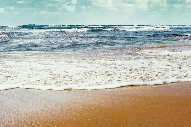 Blauwe golven op een zandstrand