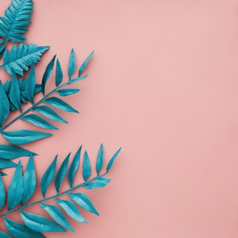 Blauwe grensbladeren op roze achtergrond met copyspace
