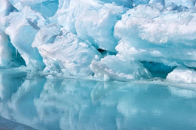 Blauwe growler stuk ijsberg met reflectie in kalm water. arctische oceaan