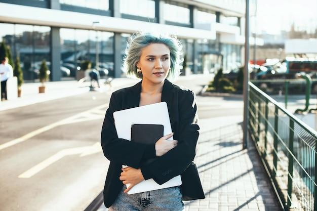 Blauwe haired kaukasische vrouw die in de straat met laptop loopt en weg kijkt