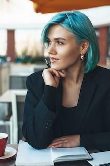 Blauwe haired zakenvrouw wegkijken zittend in een cafetaria en het lezen van een boek