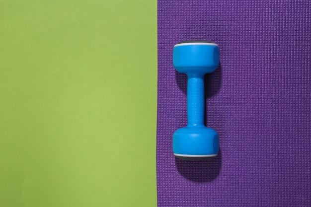 Blauwe halter en fitnessmat op groene backround met kopieerruimte. trainingsconcept.