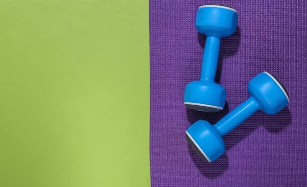 Blauwe halters en fitnessmat op groene backround met kopieerruimte. trainingsconcept.
