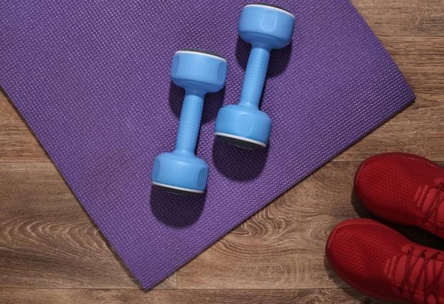 Blauwe halters, rode sportschoenen en fitnessmat op houten vloer. trainingsconcept.