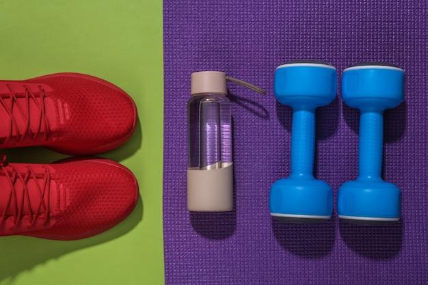 Blauwe halters, sneakers, waterfles en fitnessmat op groene backround. trainingsconcept.