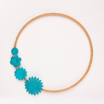 Blauwe handgemaakte bloem op het houten cirkelkader dat op witte achtergrond wordt geïsoleerd