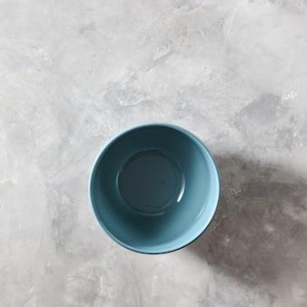 Blauwe handgemaakte chinese kom blauwe kleur op grijze stenen muur met kopie ruimte. plat leggen