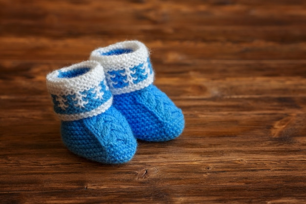 Blauwe handgemaakte gehaakte babybuiten op houten achtergrond