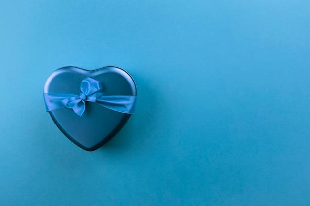 Blauwe hartvormige doos met lint op blauwe achtergrond. bovenaanzicht, kopie ruimte