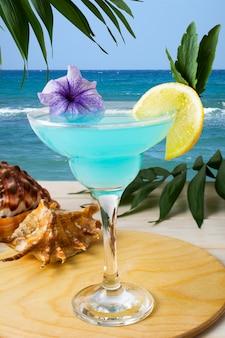 Blauwe hawaiiaanse cocktail op het tropische strand