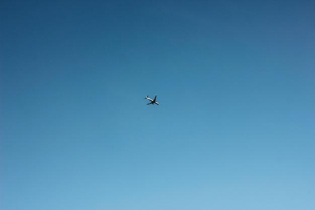 Blauwe heldere hemel met vliegend vliegtuig, achtergrond