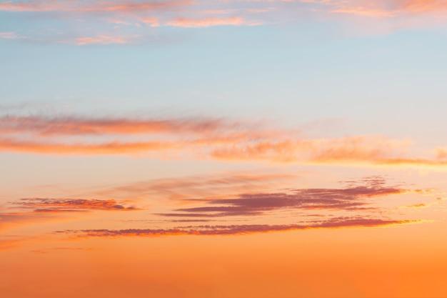 Blauwe hemel bij zonsondergang met heldere vlekken van oranje en roze