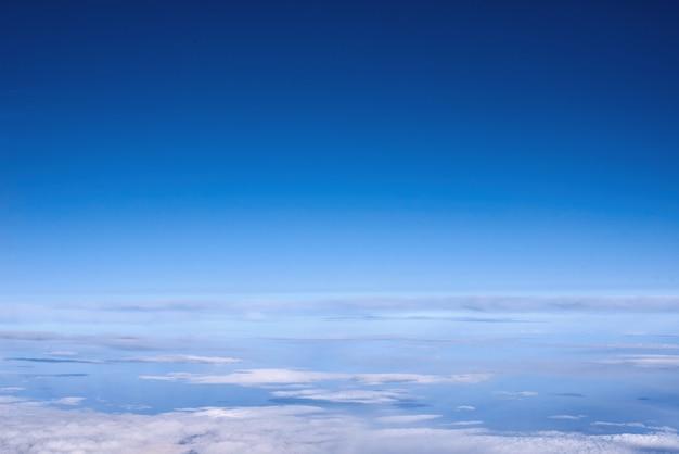 Blauwe hemel boven de wolken van vliegtuigvenster