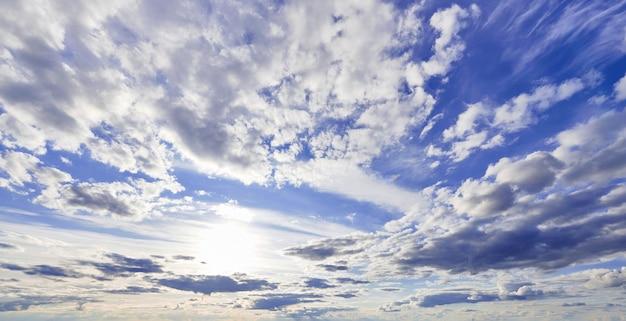 Blauwe hemel met cumulus witte wolken in de zon.