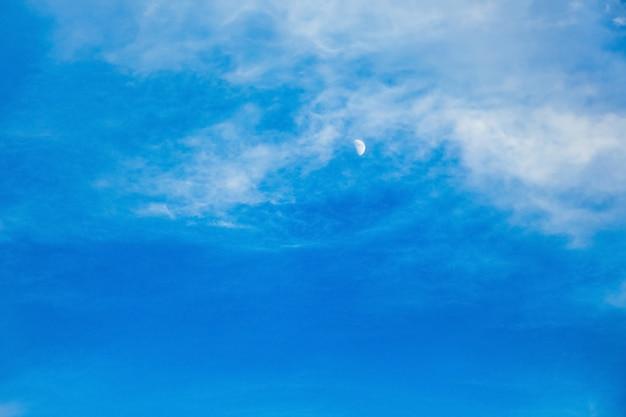 Blauwe hemel met maan en witte wolken in de avond