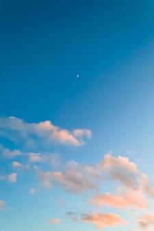 Blauwe hemel met roze wolken en vroege maan