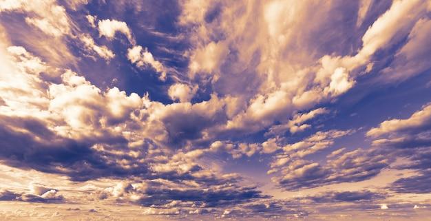 Blauwe hemel met stapelwolken bij zonsondergang.