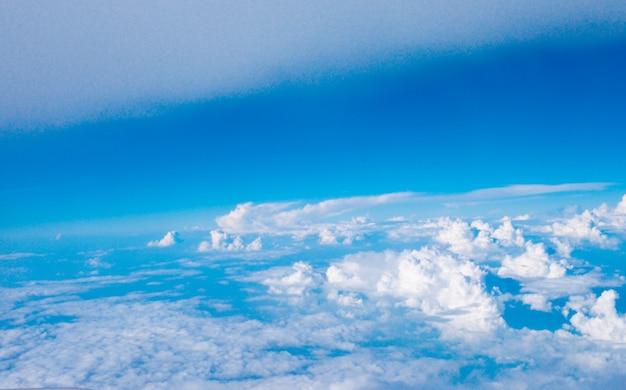 Blauwe hemel met wolken en zon op vliegtuig bekijken.