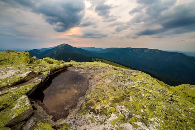 Blauwe hemel weerspiegeld in klein meer op rotsachtige bergpiek op blauwe bergketen bij dageraad.