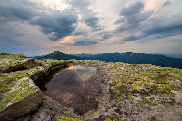 Blauwe hemel weerspiegeld in klein meer op rotsachtige bergpiek op blauwe bergketenachtergrond bij dageraad.