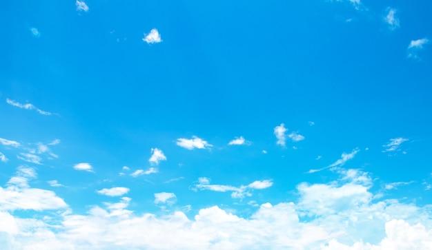 Blauwe hemelachtergrond met kleine wolken