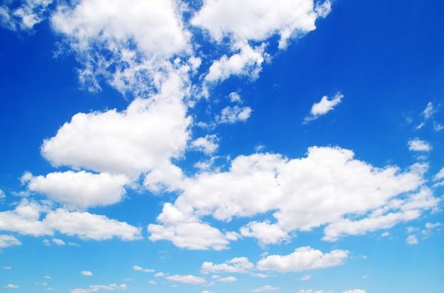 Blauwe hemelachtergrond met kleine wolken.
