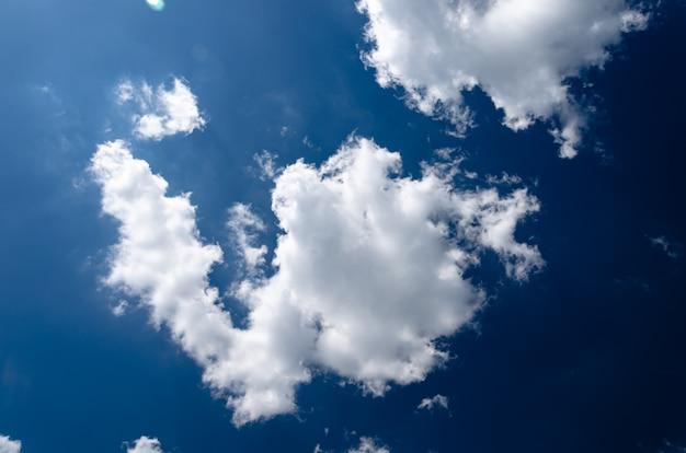 Blauwe hemelachtergrond met kleine wolkendag