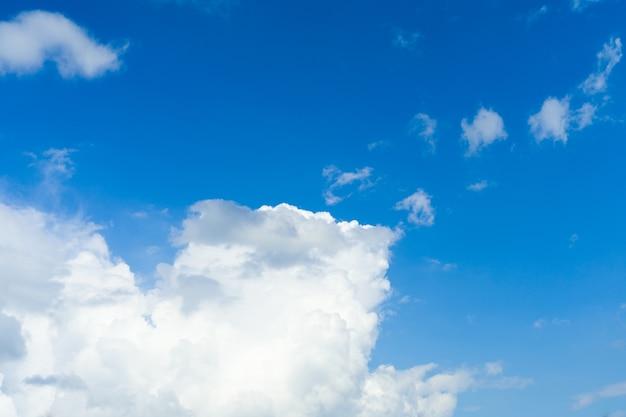Blauwe hemelachtergrond met wit pluizig wolkenbeeld