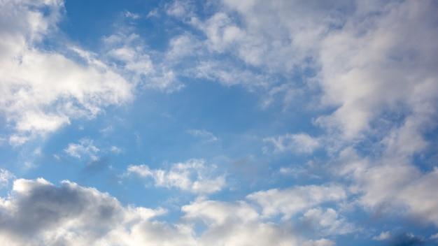 Blauwe hemelachtergrond met witte en grijze wolken. breed 16: 9