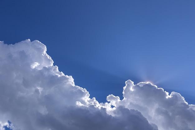 Blauwe hemelachtergrond met witte wolken op zonnige dag.