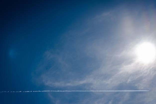 Blauwe hemelachtergrond met zonnestralen en vliegtuigslepen die de hemel kruisen.