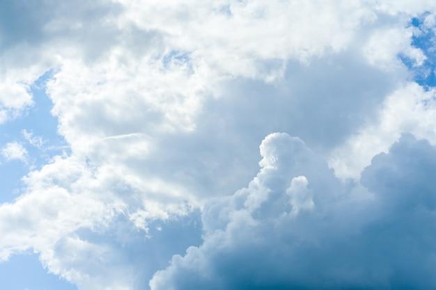 Blauwe hemelruimte met witte pluizige wolken
