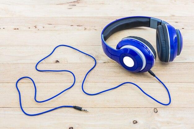 Blauwe hoofdtelefoons op houten bureau.