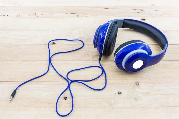 Blauwe hoofdtelefoons op houten bureau