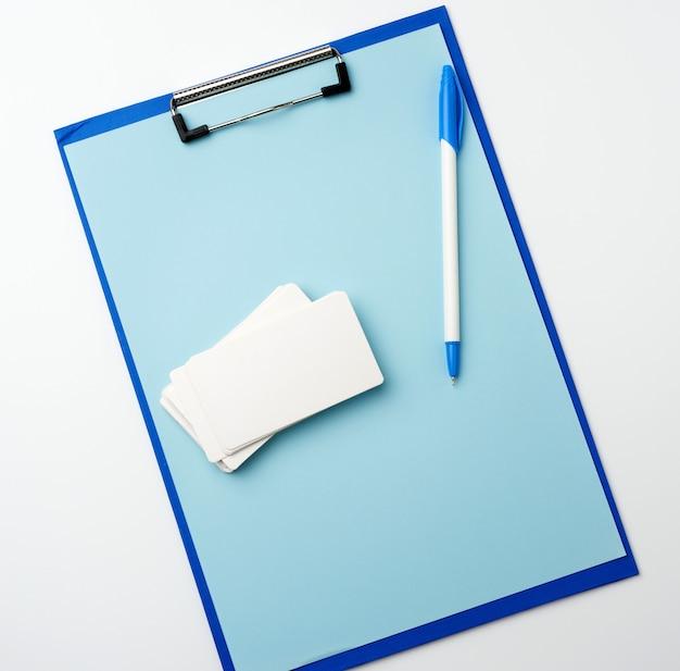 Blauwe houder met schone blauwe lakens, pen, leeg visitekaartje op een witte achtergrond