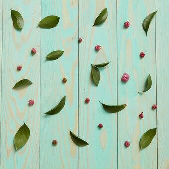 Blauwe houten achtergrond versierd met bladeren en bloemen plat leggen