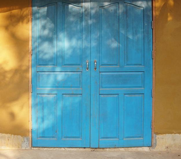 Blauwe houten deur en gele muur van aardehuis