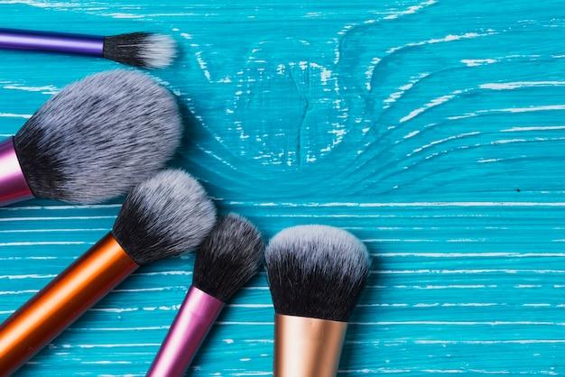 Blauwe houten oppervlak met decoratieve make-up kwasten