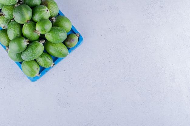Blauwe houten schotel gevuld met een hoop feijoa's op marmeren achtergrond. hoge kwaliteit foto