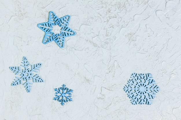 Blauwe houten sneeuwvlokken op lichte achtergrond