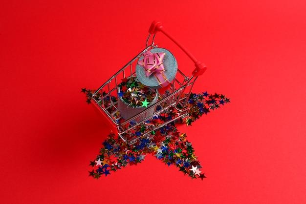 Blauwe huidige doos met roze strik in een winkelwagentje en confetti op een rode achtergrond.