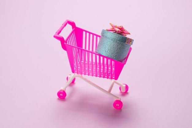 Blauwe huidige doos met roze strik in een winkelwagentje