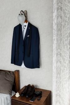 Blauwe huwelijkskledij voor een bruidegom die op de muur hangt