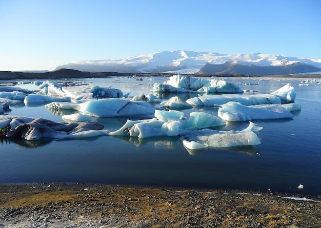 Blauwe ijsbergen die in jokulsarlon-gletsjerlagune drijven, de vroege winter in zuid-ijsland