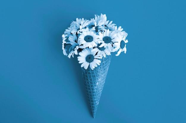 Blauwe ijsje met kamilles in het midden van de blauwe achtergrond. bovenaanzicht. kopieer ruimte. lente of zomer bloemen concept.