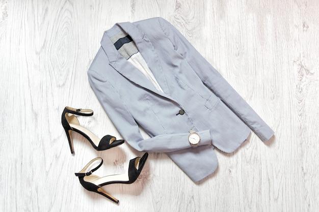 Blauwe jas, horloge en zwarte schoenen